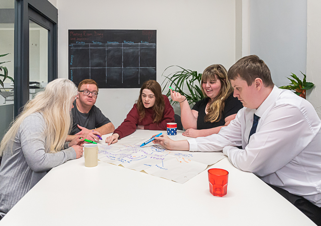 Five young people sat around a table looking a sheet of paper on which they are drawing a mind-map.