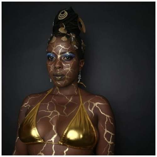 Chanje Kunda looks thoughtfully off camera with gold paint on her face in the style of Kiinstsugi, which imitates gold cracks