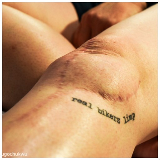 Close up of a knee with a scar on it, as well of a tattoo that reads 'real bikers limp'