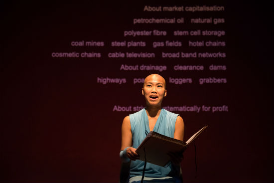 A photo of a woman on stage in a blue dress seen from the waste up reading from a large book. Behind her text is projected onto a red wall.