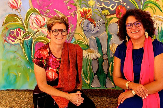 A colourful painting. In front of it sits artist Rachel Gadsden and ethnographer Dr. Yafa Shanneik