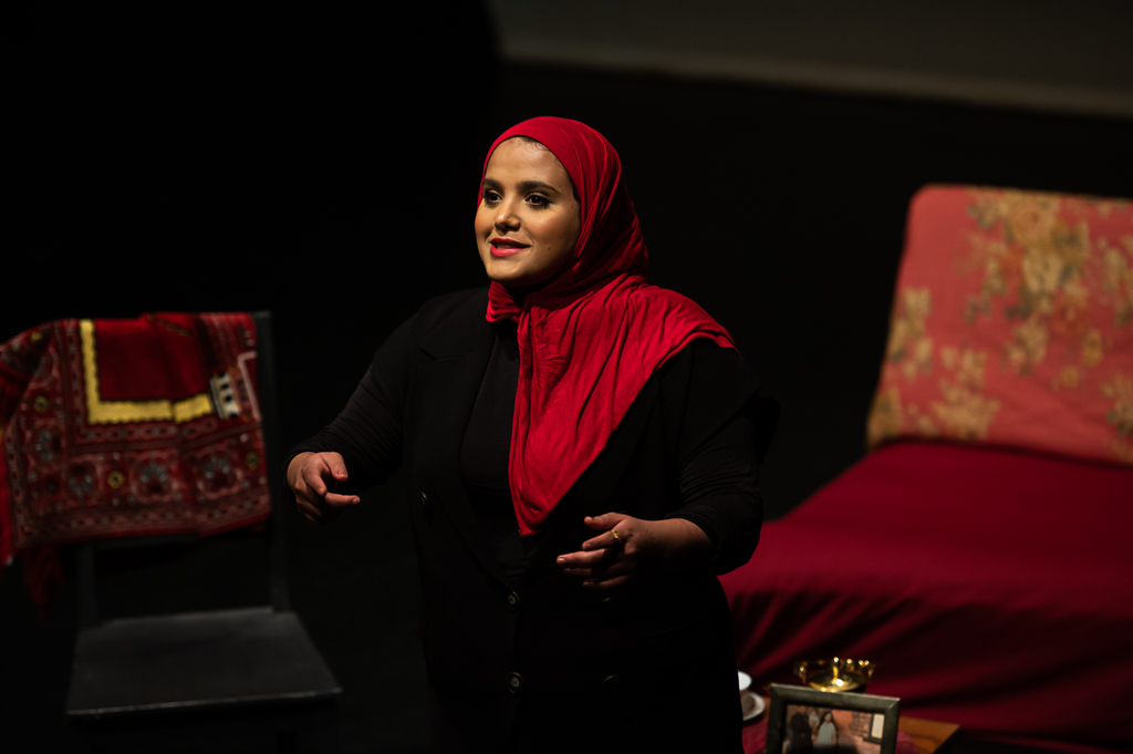 Amina Atiq wearing a black outfit and red hijab addressing an audience earnestly.