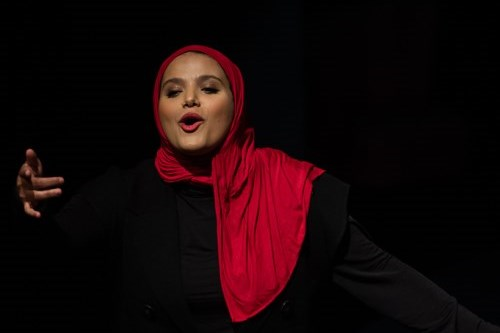 Amina Atiq, a performer wearing a red hijab and black outfit, regales the audience.