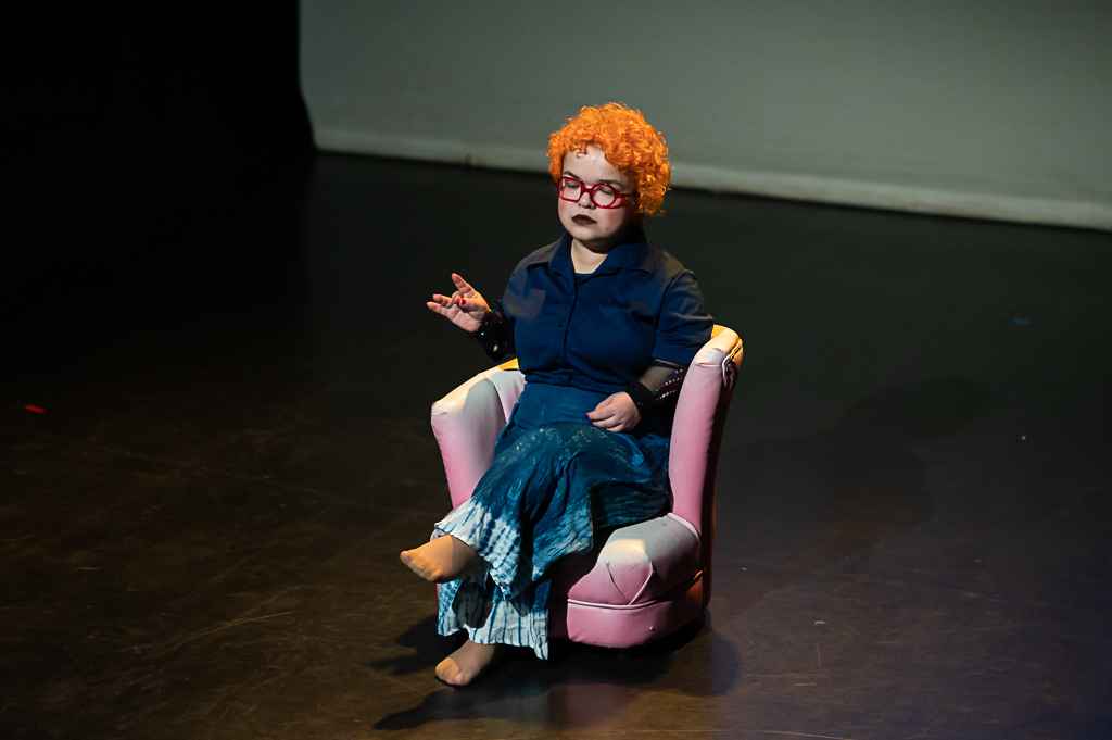 Tammy Reynolds sits on stage in a chair, eyes closed, her hair bright orange.