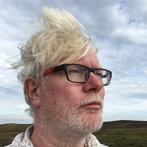 Aidan Moesby wearing glasses standing against against a blue sky with wind blowing his hair
