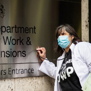 Dolly sens in doctor coat and mask putting a thermometer against the sign of the Department of Work and Pensions