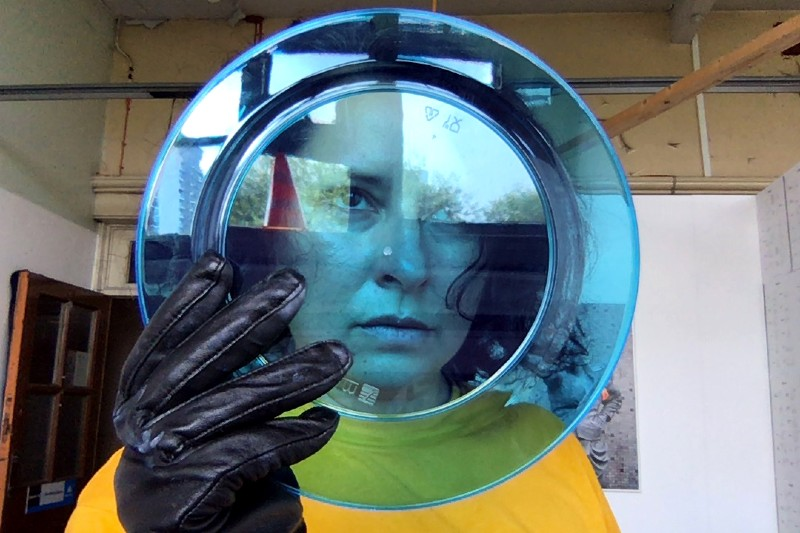 Nicola looks through a transparent blue plate holding the plate with a black leather glove, she looks dreamily off screen.