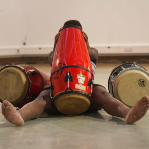 A black man sitting on the floor is obscured by three drums