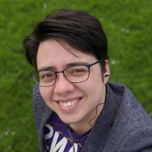 Image description: A photo of Julian against a grassy background; he is smiling at the camera. Julian is a mixed Chinese-white man in his twenties