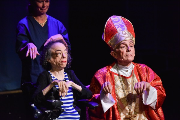 Woman in wheelchair on stage holding her hands in mid air next to a man dressed as a priest