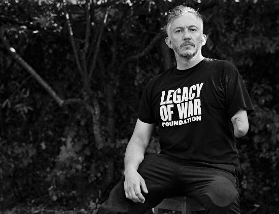 A black and white photo of Giles Duley sitting on a chair and wearing a t-shirt with the slogan Legacy of War Foundation