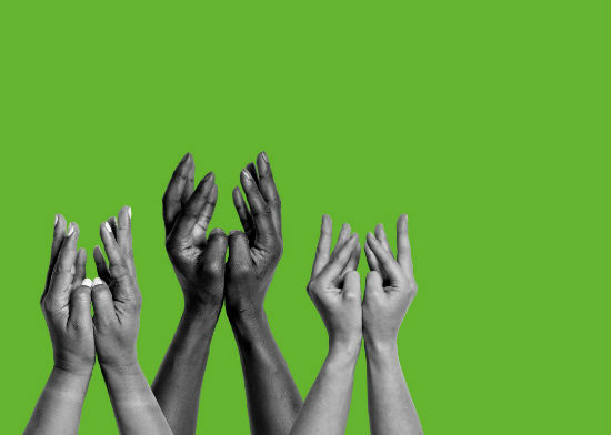 a photograph of hands reaching into the air on a green background.