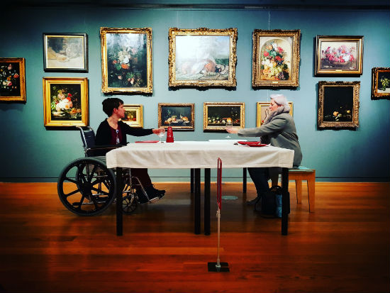 A woman sits across a table from a man in a wheelchair. They are raising a glass to each other. Behind them is a wall covered in paintings.