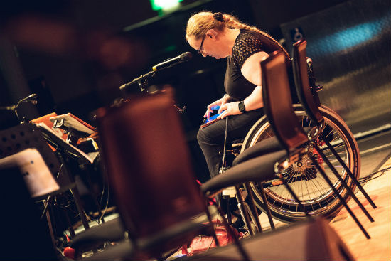 A woman in a wheelchair works on a tablet. In front of her is a microphone and to the left are music stands.