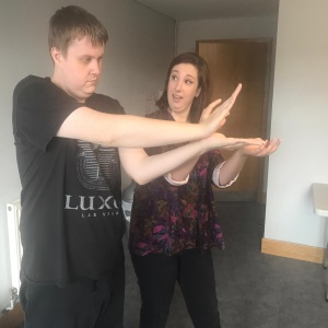 An image of a young man making shapes with his arms and hands. A young woman is next to him and looks like she is guiding him