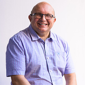 A portrait photo of a man against a white background, smiling happily to camera wearing glasses and a striped short sleeved shirt