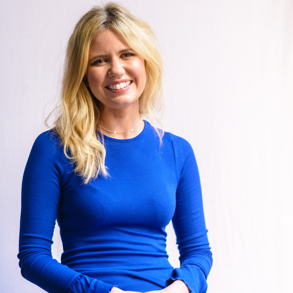 A photo of a young woman with blond hair against a white background. She is wearing a blue dress and is smiling to the camera