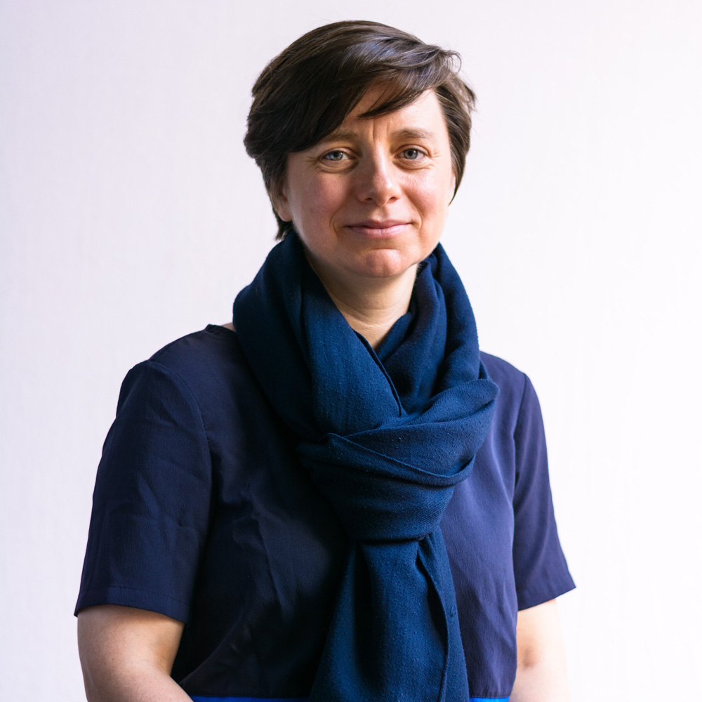 A photo of a woman with short, dark hair wearing a dark blue t-shirt and a blue scarf