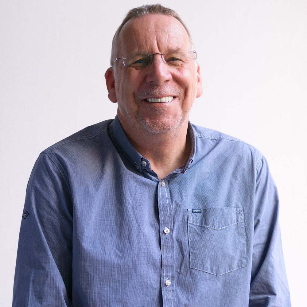 A photo of a man against a white background. He is wearing glasses and a blue shirt
