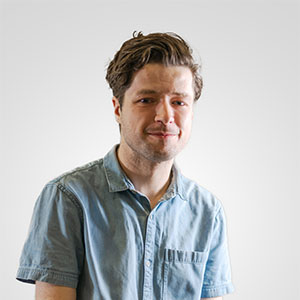 A photo of a young man wearing a light blue short sleeved shirt against a white background