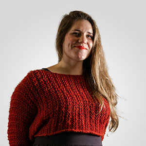A photo of a young woman with long brown hair, wearing a red sweater and smiling to camera