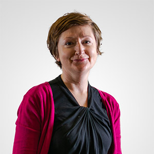 A photo of a woman with short brown hair wearing a black top and a pink cardigan against a white background