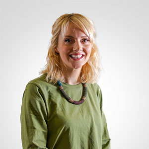 A photo of a woman with shoulder length blond hair wearing a green dress and a beaded necklace.