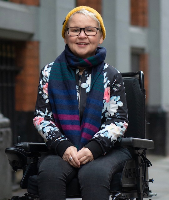 Nickie smiles into camera - she is outdoors wearing a woolly pullover and scarf.. Nickie is a wheelchair user.